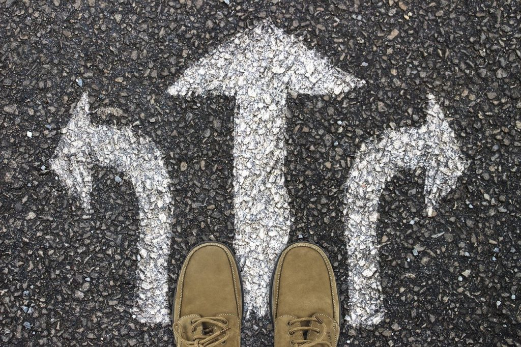 Closeup of feet standing on 3 chalk arrows representing a decision
