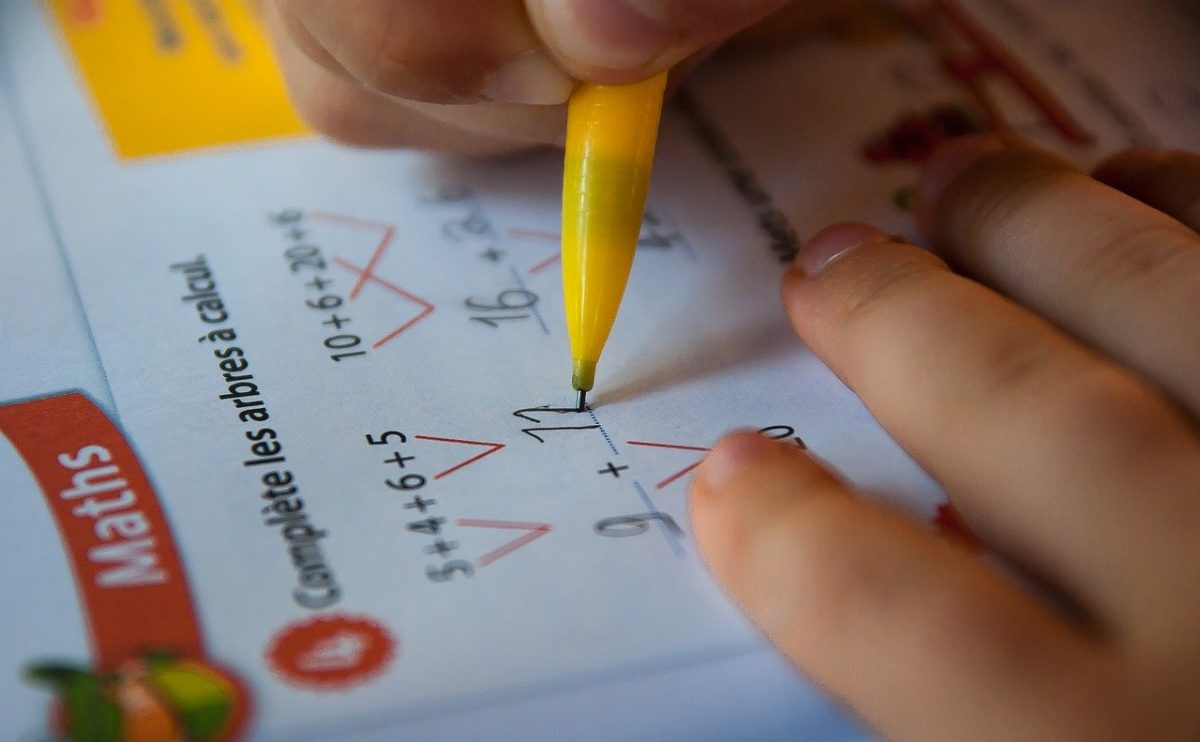 Close up of person holding a pencil performing longform calculations