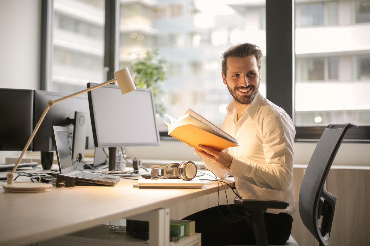 Smiling man holding a book in an office