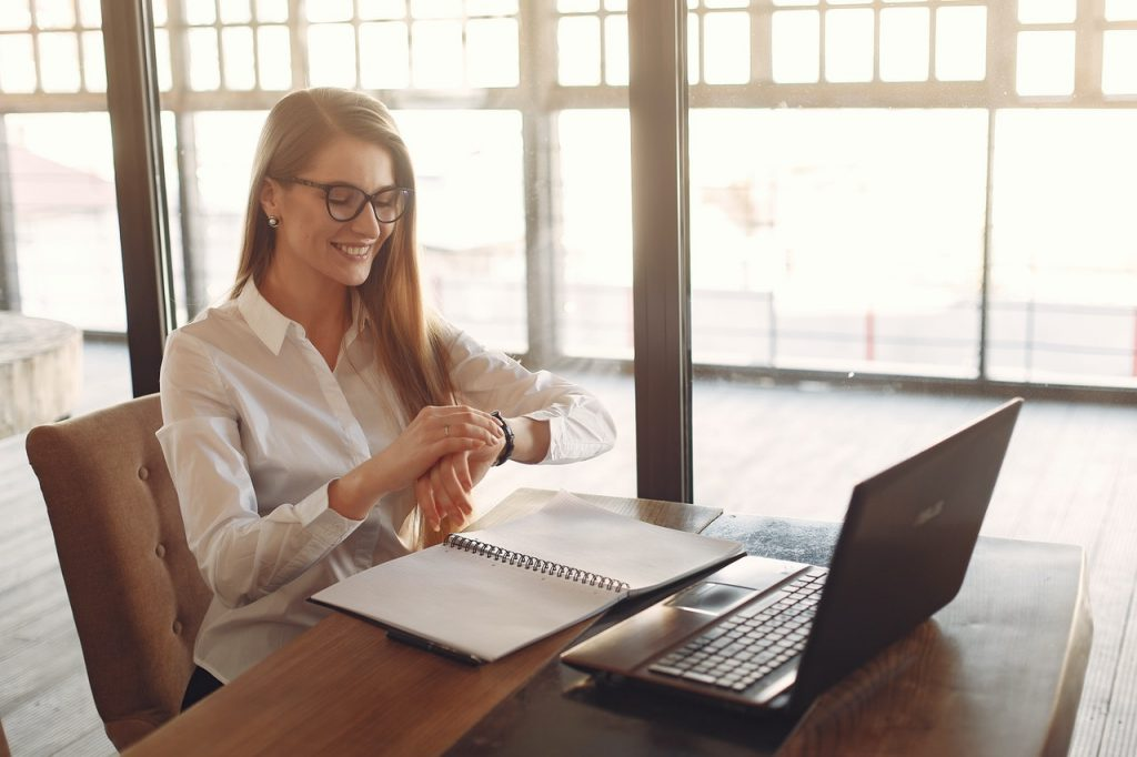 Blond woman with glasses working with a laptop