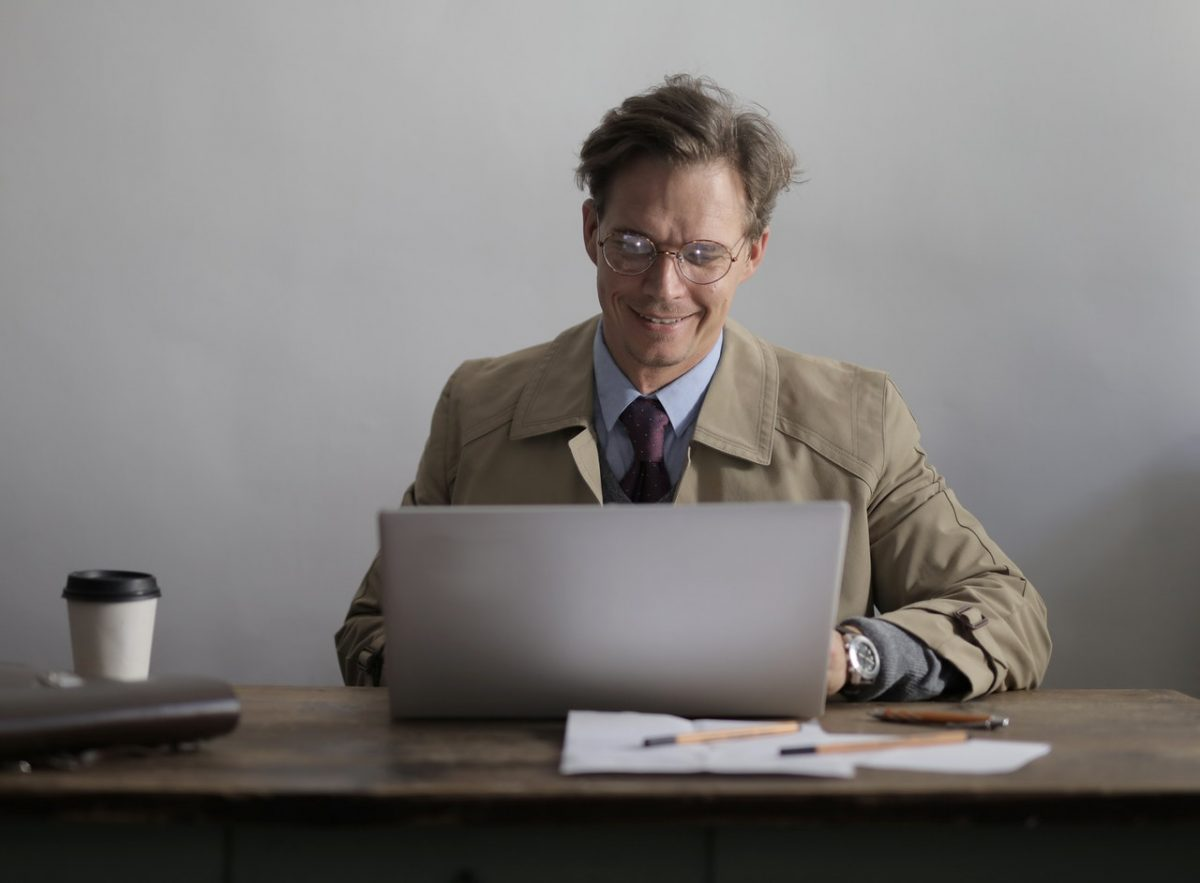Man in a suit and overcoat using a laptop