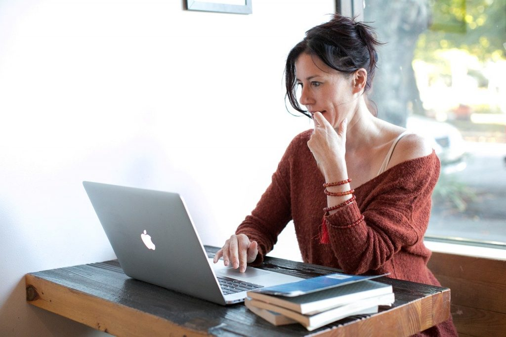 Attractive woman in red sweater working at a computer