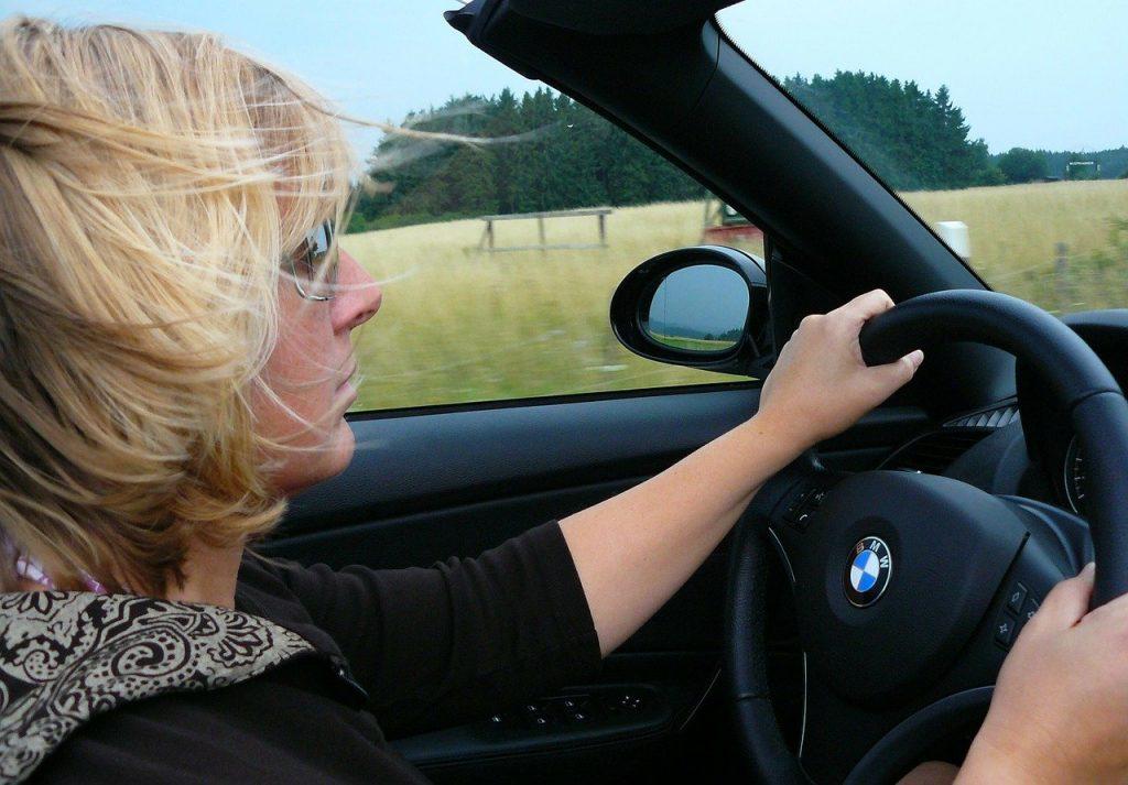 Blonde woman driving a BMW convertible