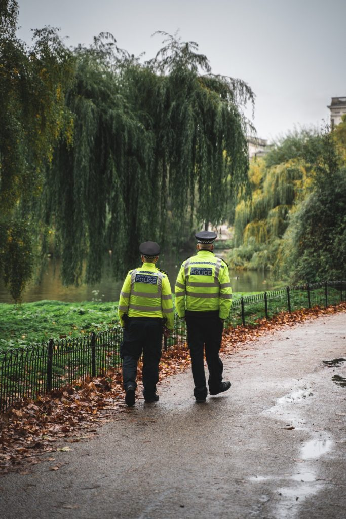 Police officers wearing florescent yellow vests walking through a park