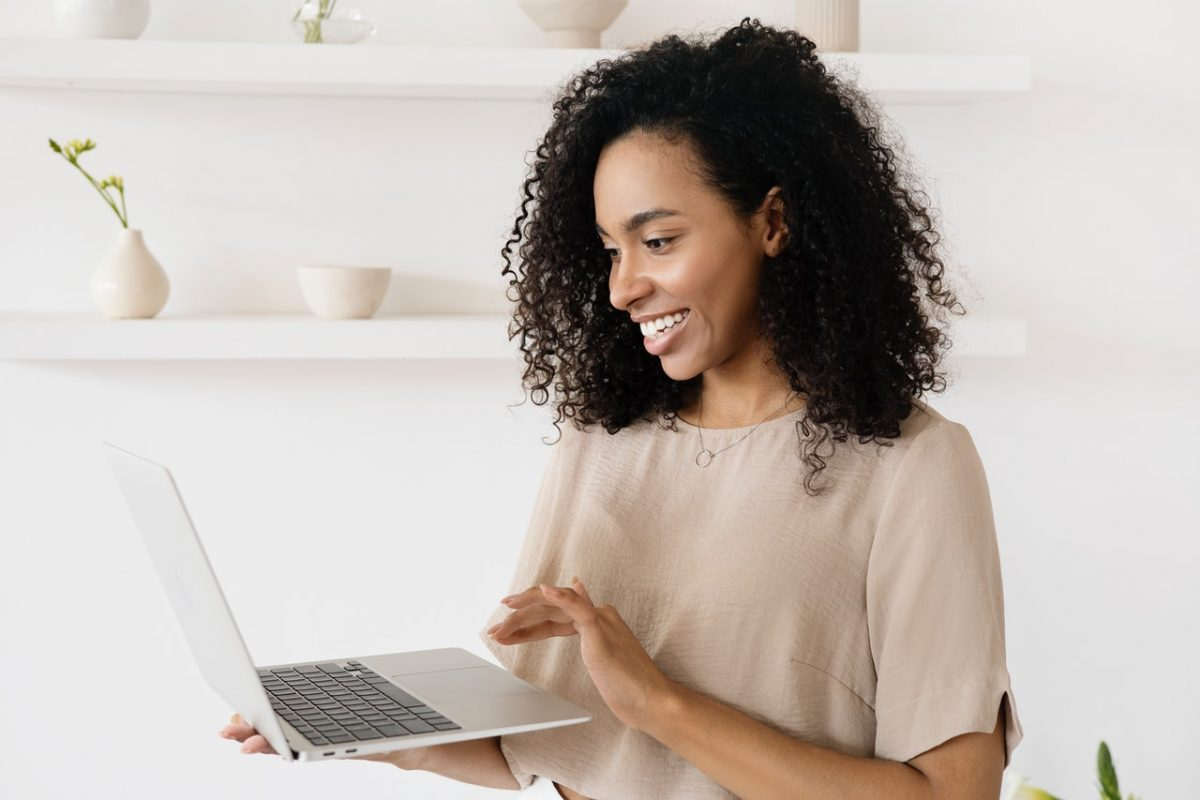 Smiling woman composing a professional e-mail