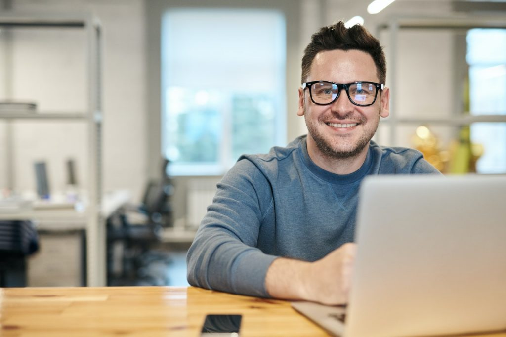 Happy man wearing glasses while working on a laptop